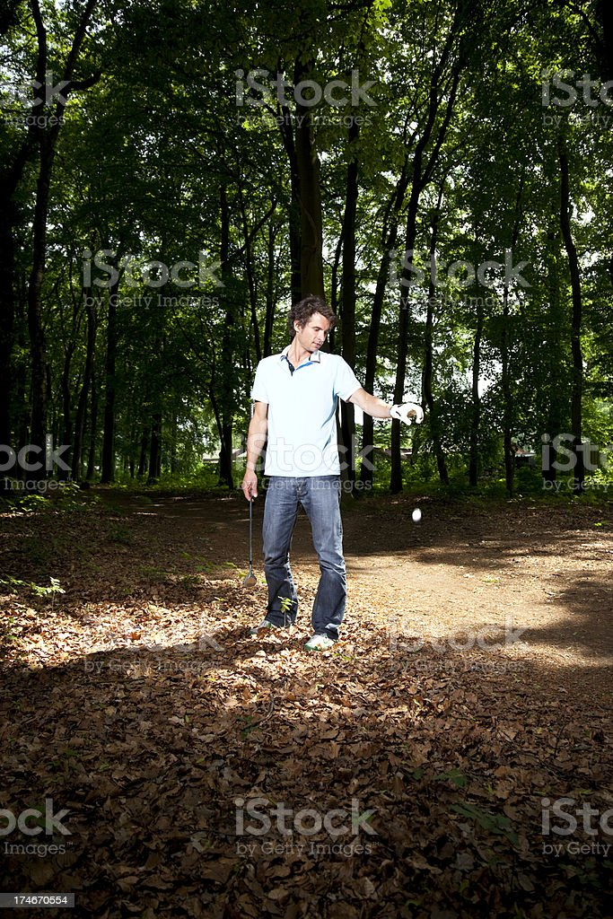 young man playing golf, dropping a ball, penalty royalty-free stock photo