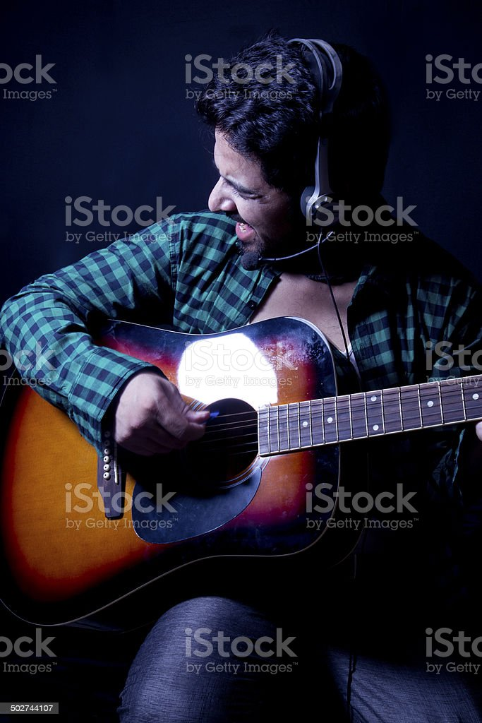 Young man playing guitar and singing stock photo
