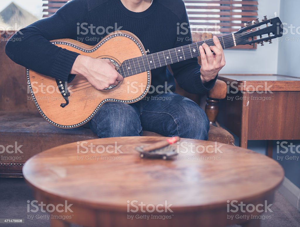 Young man playing guitar at home stock photo