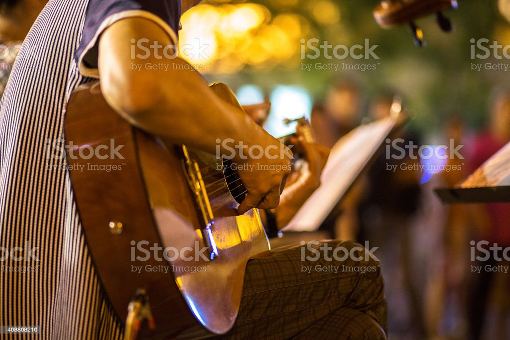 young man playing guitar on street at night stock photo