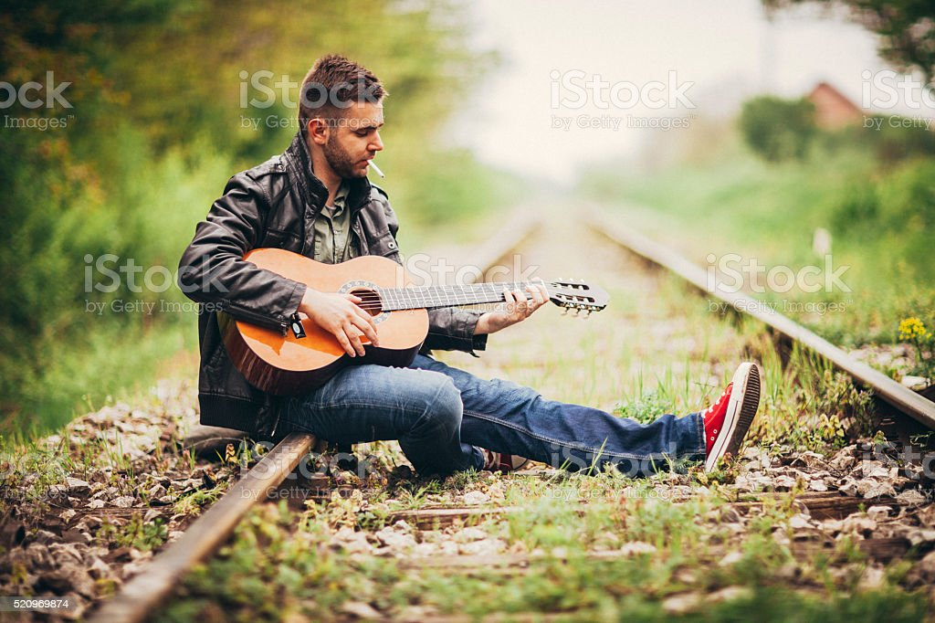 Young man playing guitar outdoors stock photo