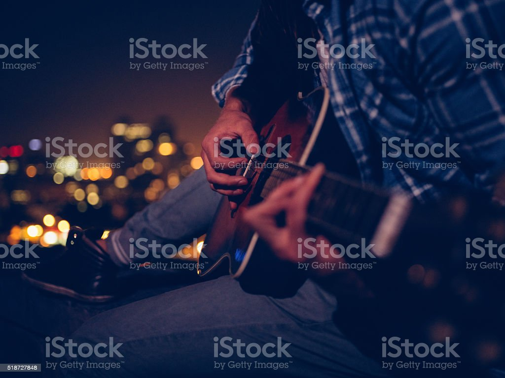 Young man playing guitar sitting on the rooftop at night stock photo