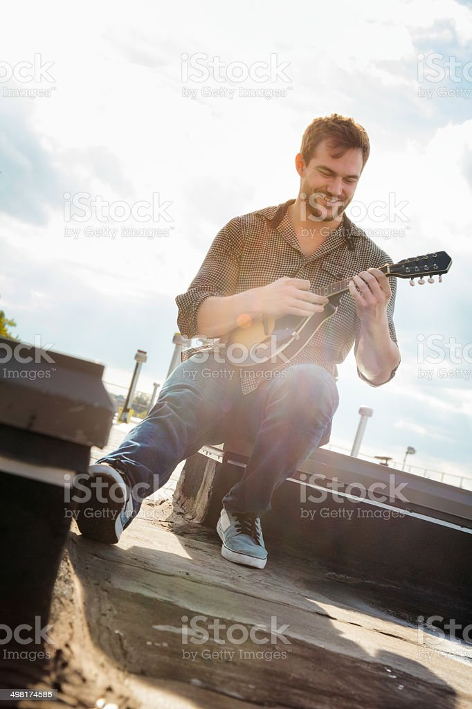 Young man playing his mandolin on Brooklyn rooftop stock photo