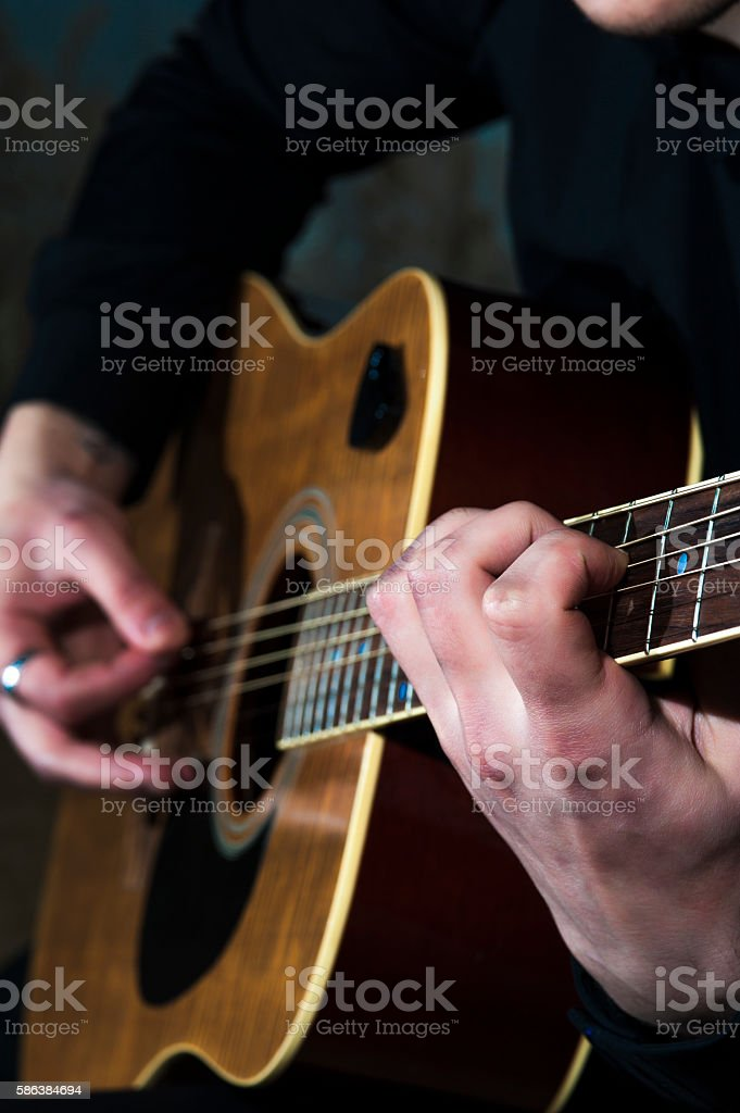 Young man playing on acoustic guitar stock photo