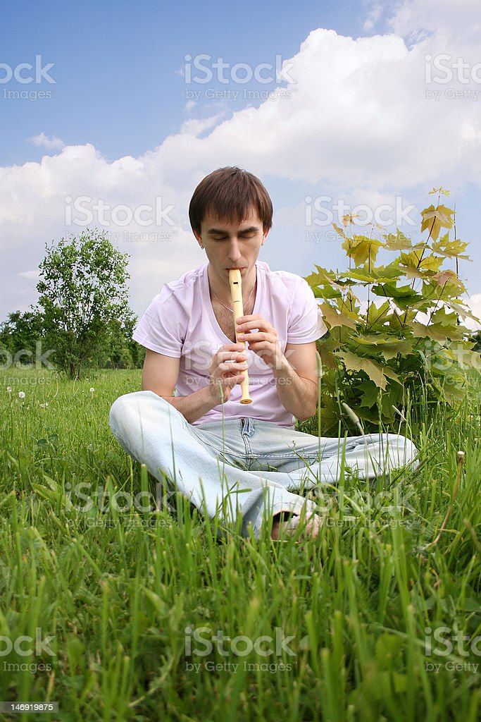 young man playing on flute at summer time royalty-free stock photo