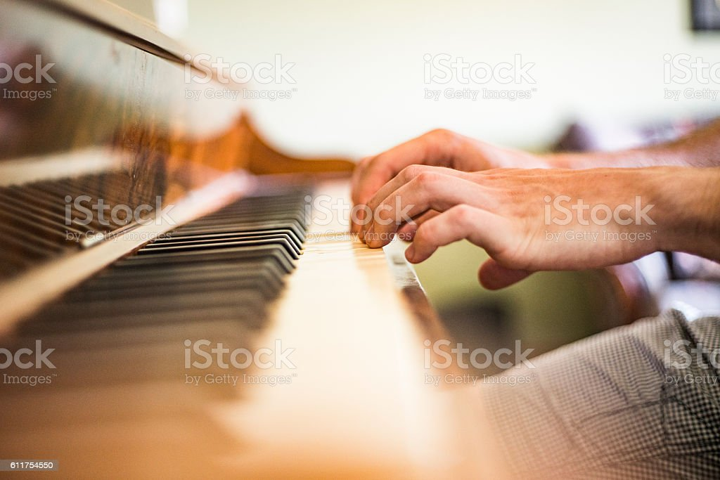 Young man playing piano. Closeup hands on keyboard stock photo