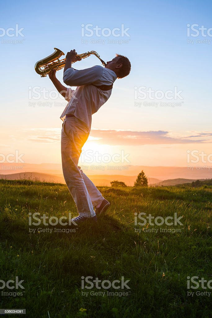 young man playing saxophone outdoor at sunset stock photo