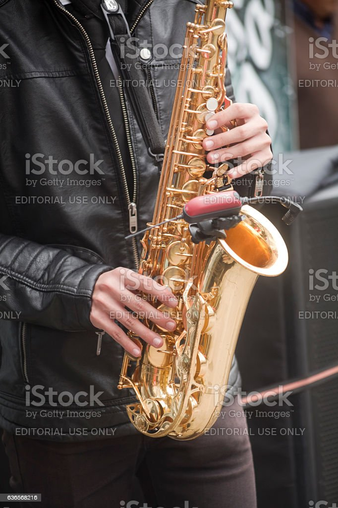 Young man playing saxophone outdoors, leather jacket. stock photo