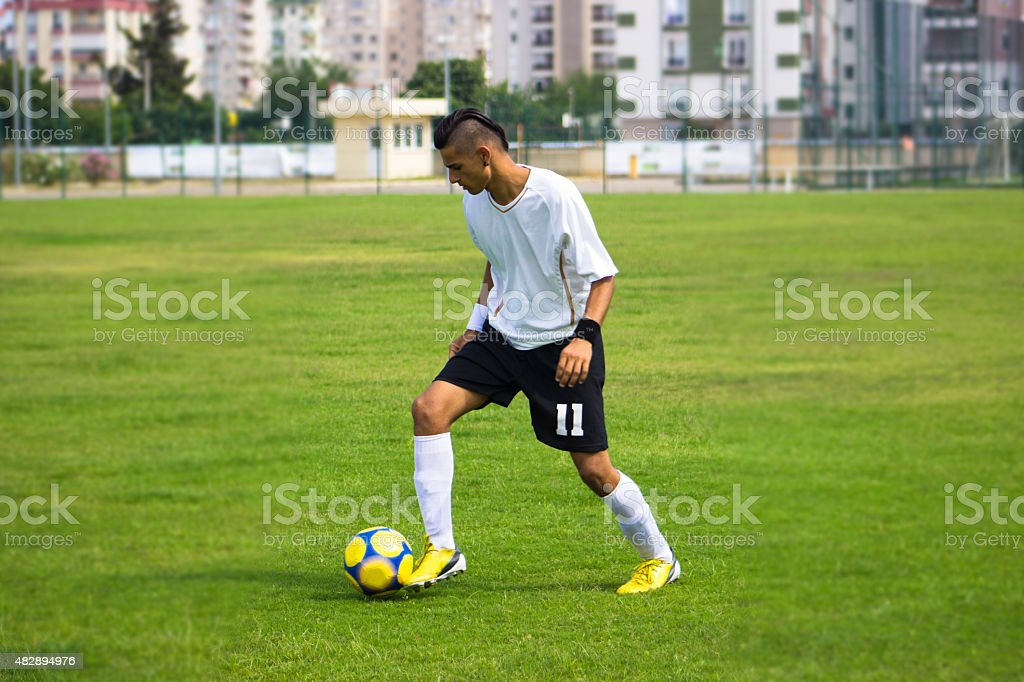 Young man playing soccer on soccer field stock photo