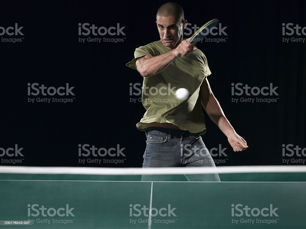 Young man playing table tennis (blurred motion) stock photo