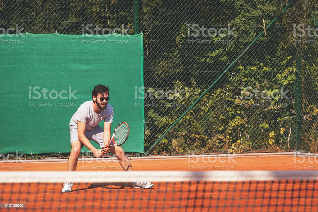 Young man playing tennis on the open court stock photo