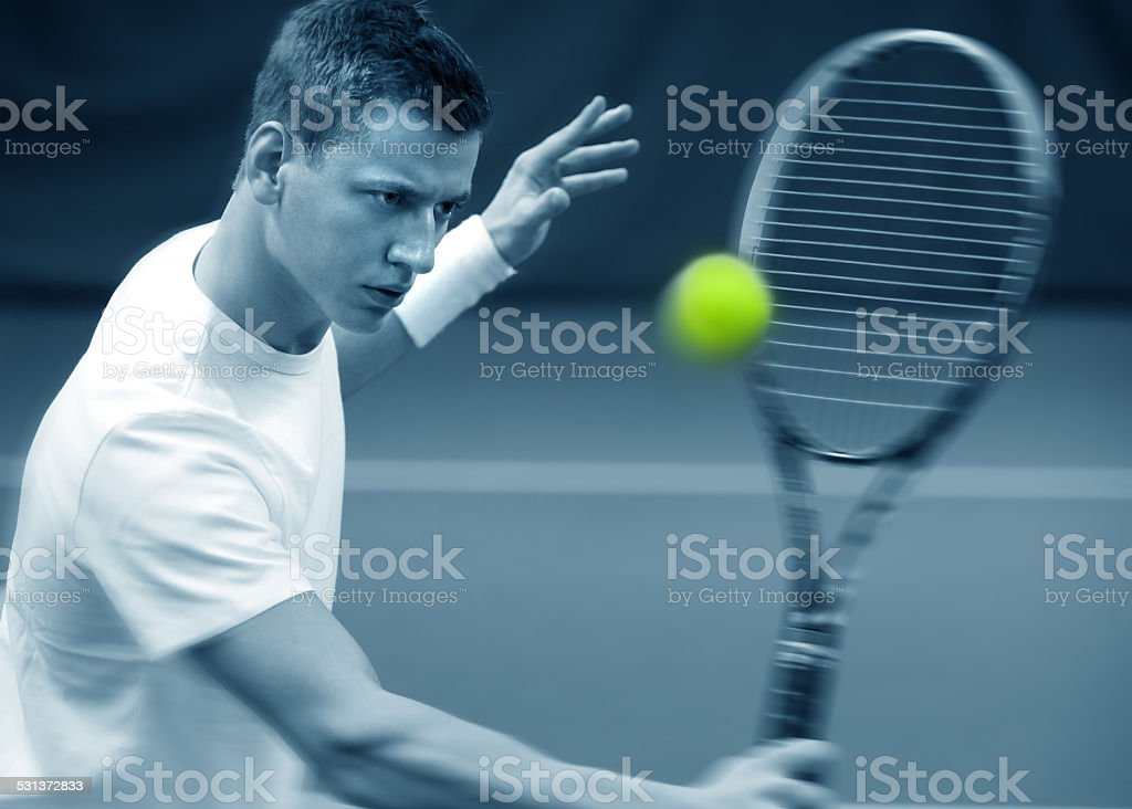 .Young man playing tennis stock photo