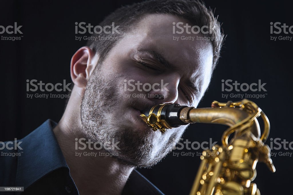 Young man playing the Saxophone. stock photo