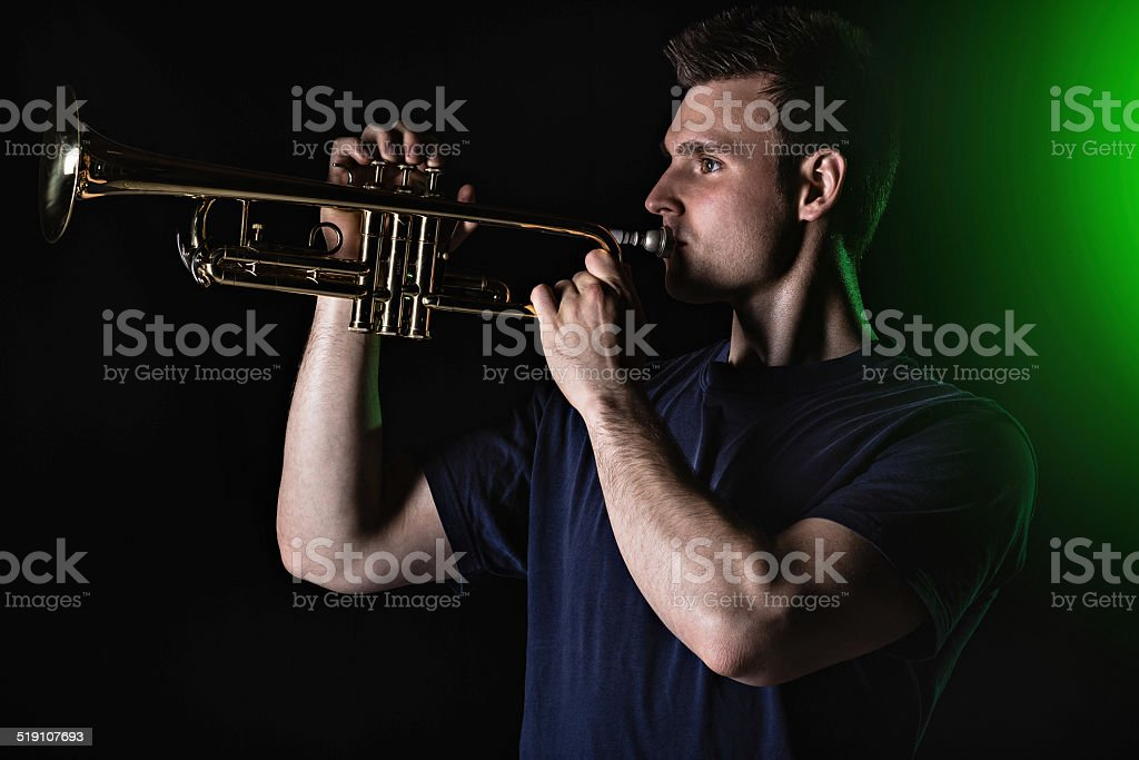 Young man playing the trumpet stock photo