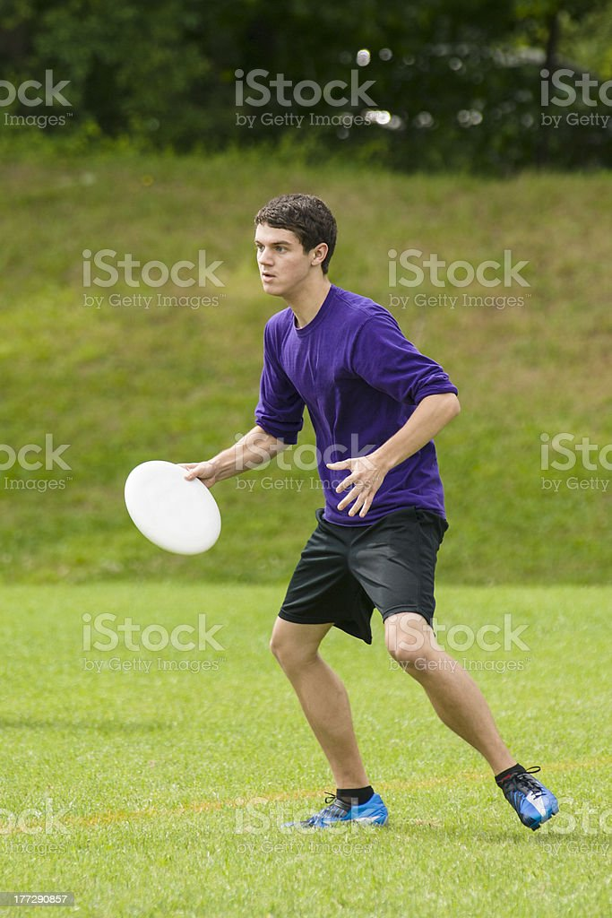 Young man playing Ultimate Frisbee on grassy field stock photo