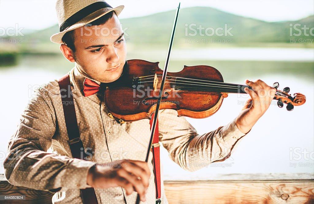 young man playing violin stock photo