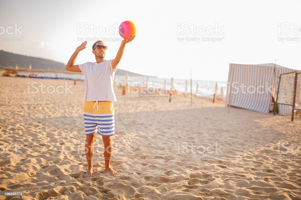 Young man playing volleyball on beach stock photo