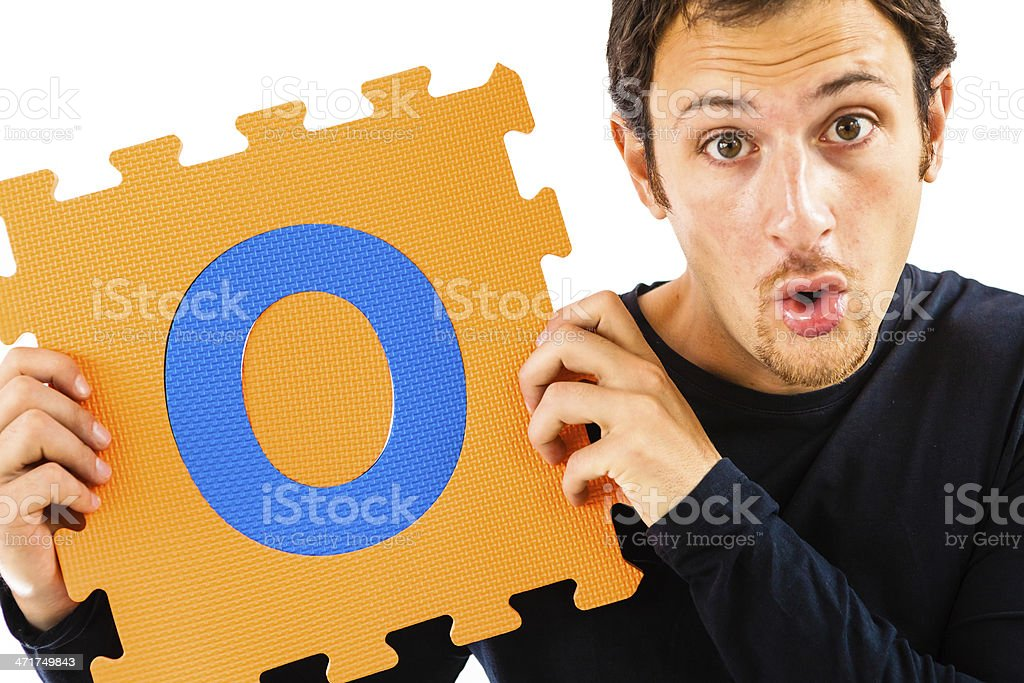 Young Man Playing with Alphabet Puzzle, Letter O royalty-free stock photo