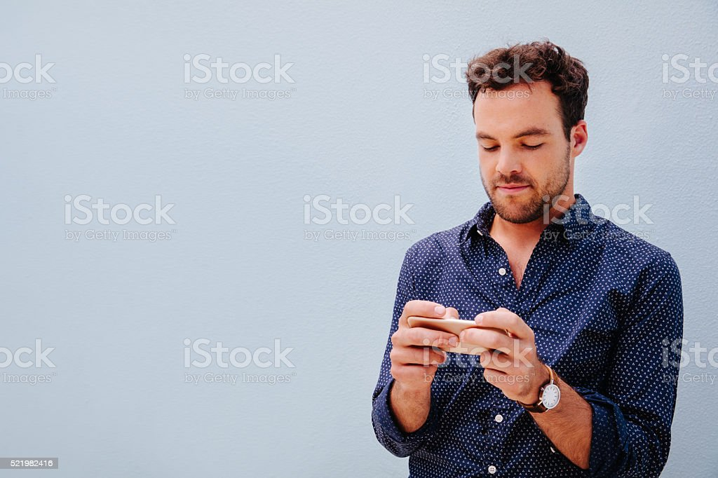 Young man plays games on the mobile phone stock photo