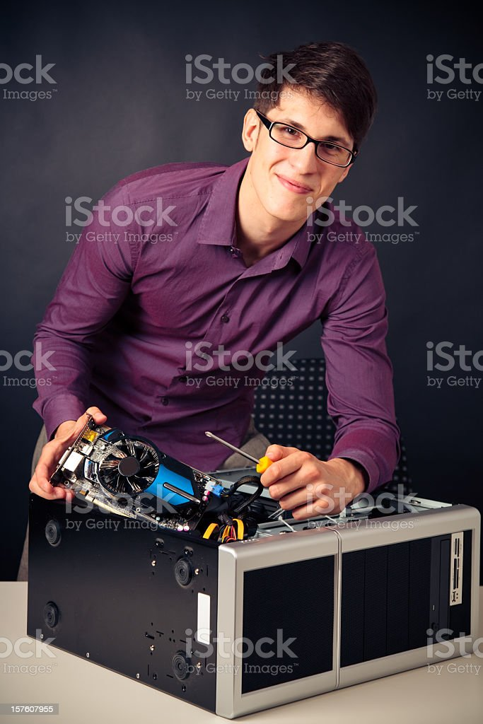 young man plugging in a new graphics card stock photo