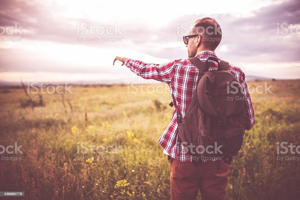 Young man point the finger in nature stock photo