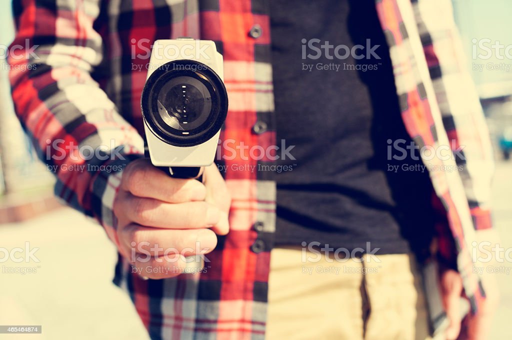 young man pointing a Super 8 camera at the observer stock photo