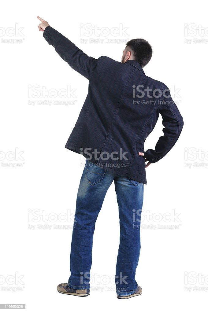 young man pointing at wall. rear view. stock photo