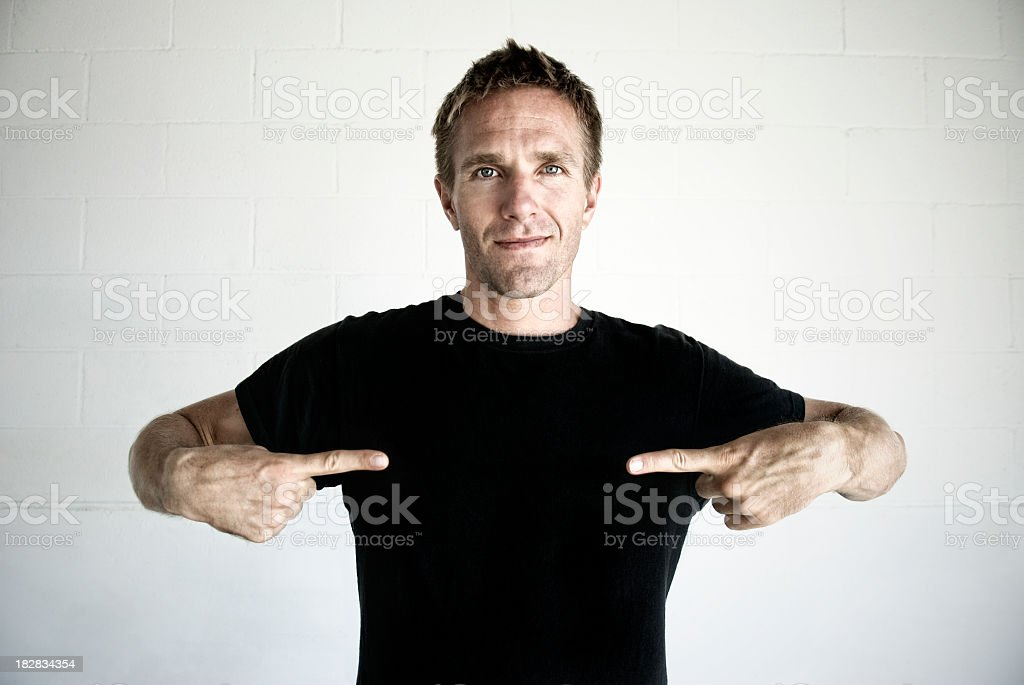 Young Man Pointing to Black T-Shirt Copy Space stock photo