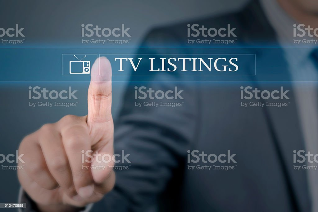 Young man pointing to TV listings stock photo