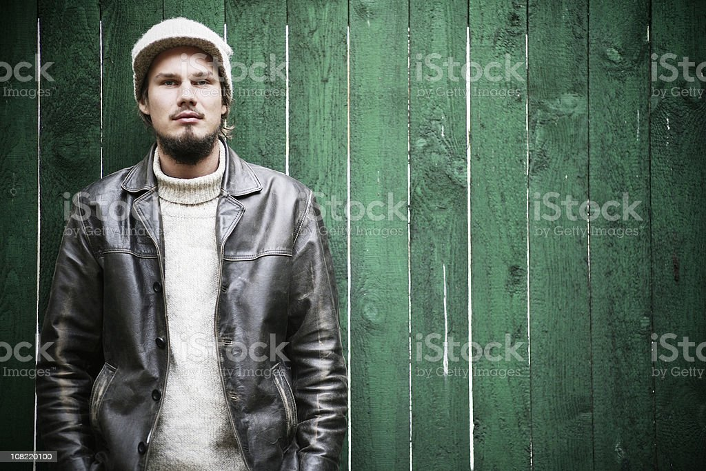 Young Man Posing Against Green Fence royalty-free stock photo