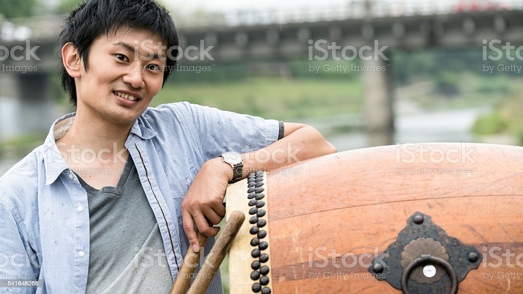 Young man posing by the Japanese drum stock photo