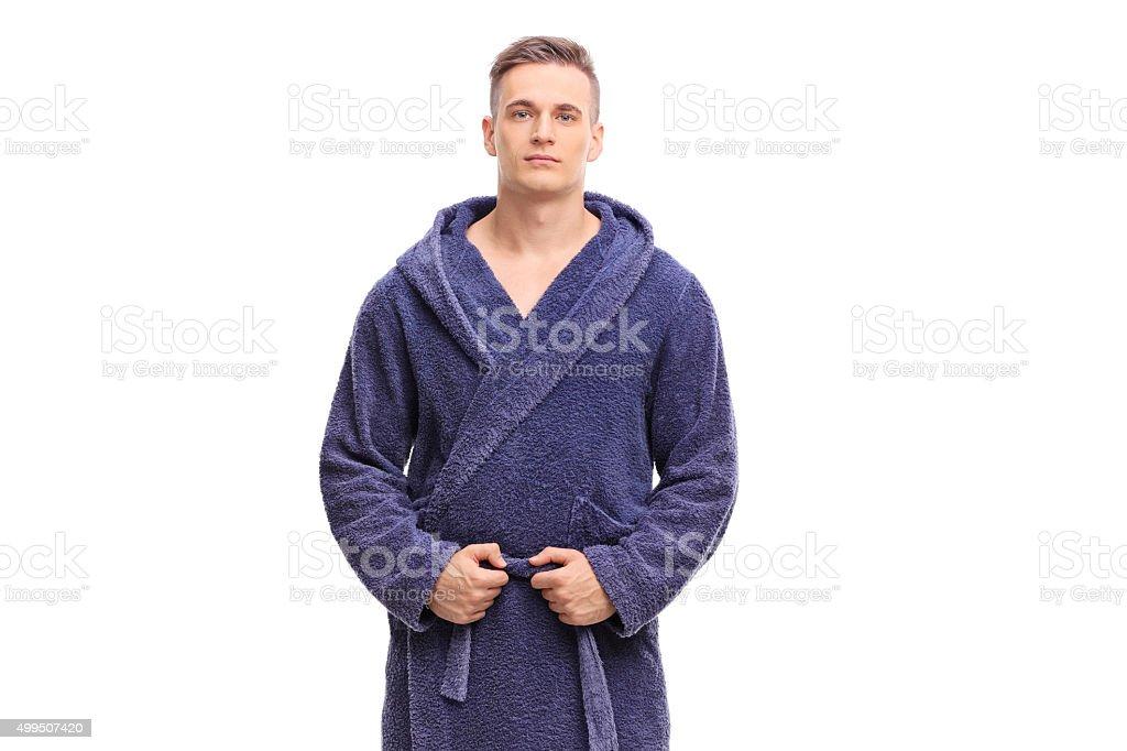 Young man posing in a blue bathrobe stock photo