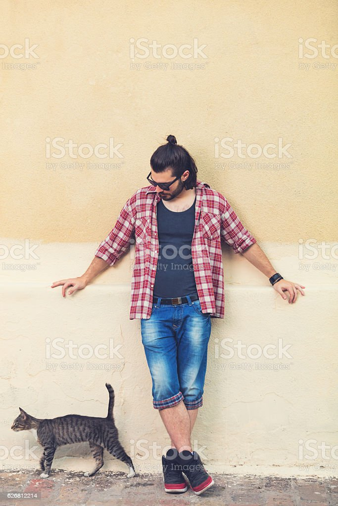 Young man posing in front of the camera with cat. stock photo