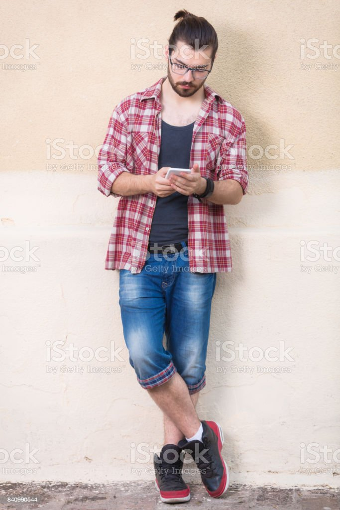 Young man posing in front of the camera with the cellphone. stock photo