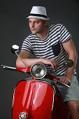 Young man posing with red motorbike