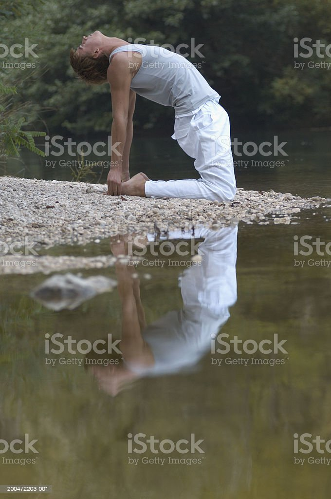 Young man practicing yoga position by river, stretching backwards stock photo