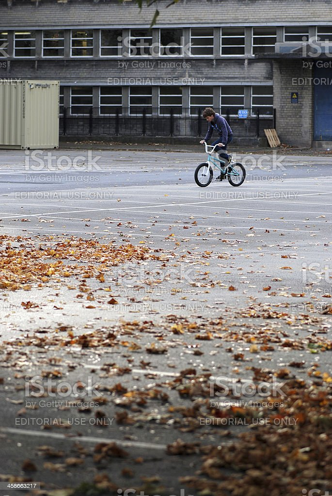 Young man practising BMX tricks in empty parking lot royalty-free stock photo