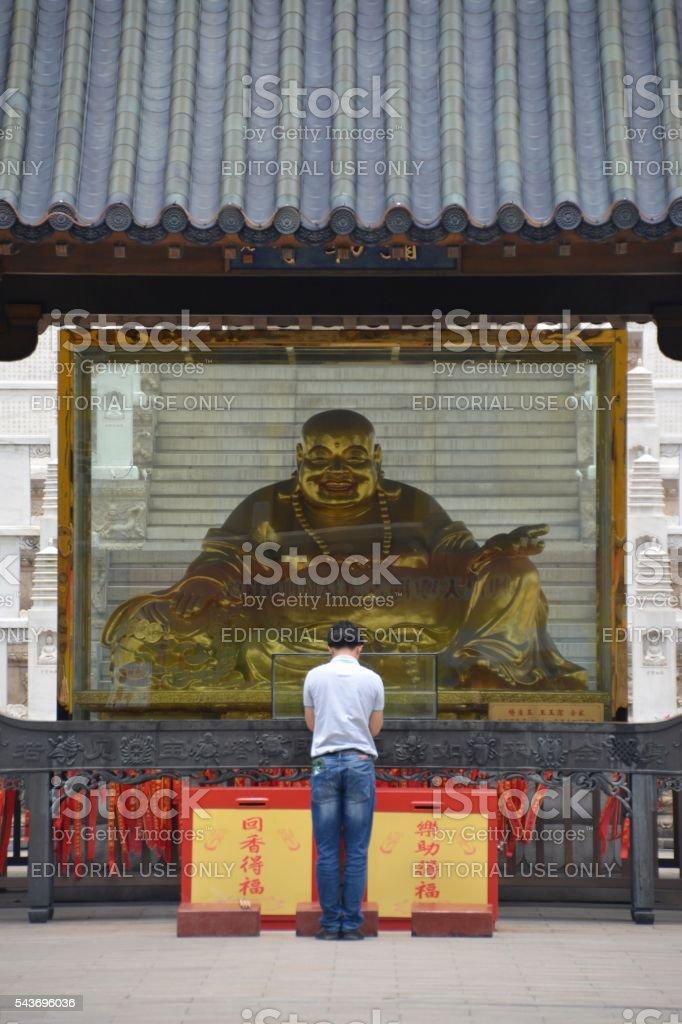 Young man praying gilded Buddha statue in Tianning temple, Changzhou stock photo