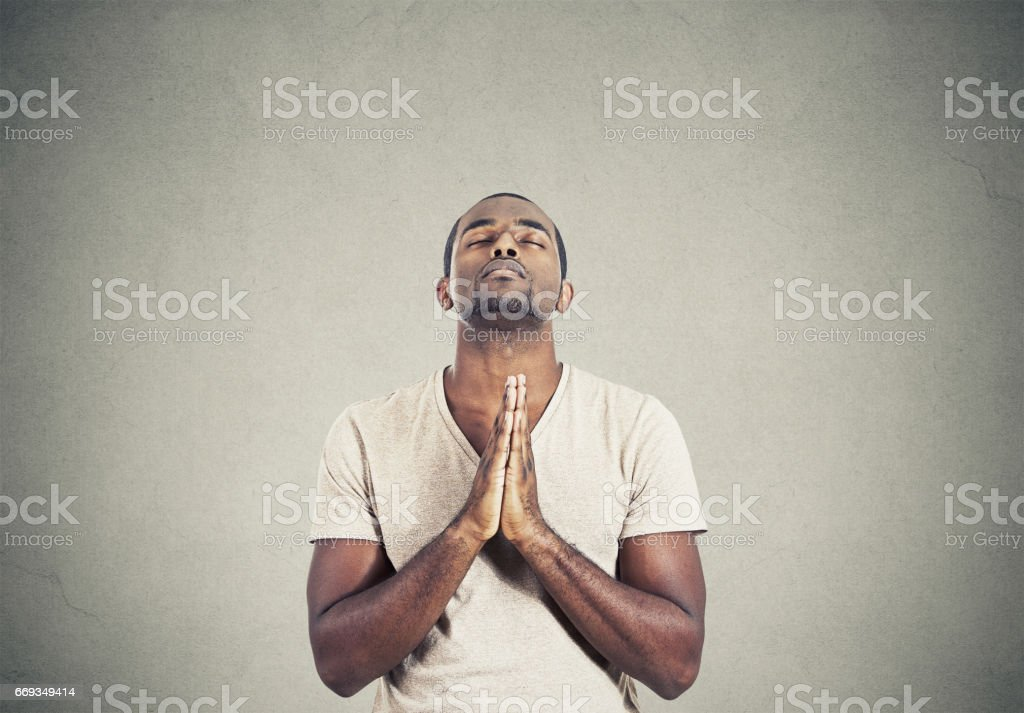 young man praying hands clasped hoping for best asking for forgiveness or miracle stock photo