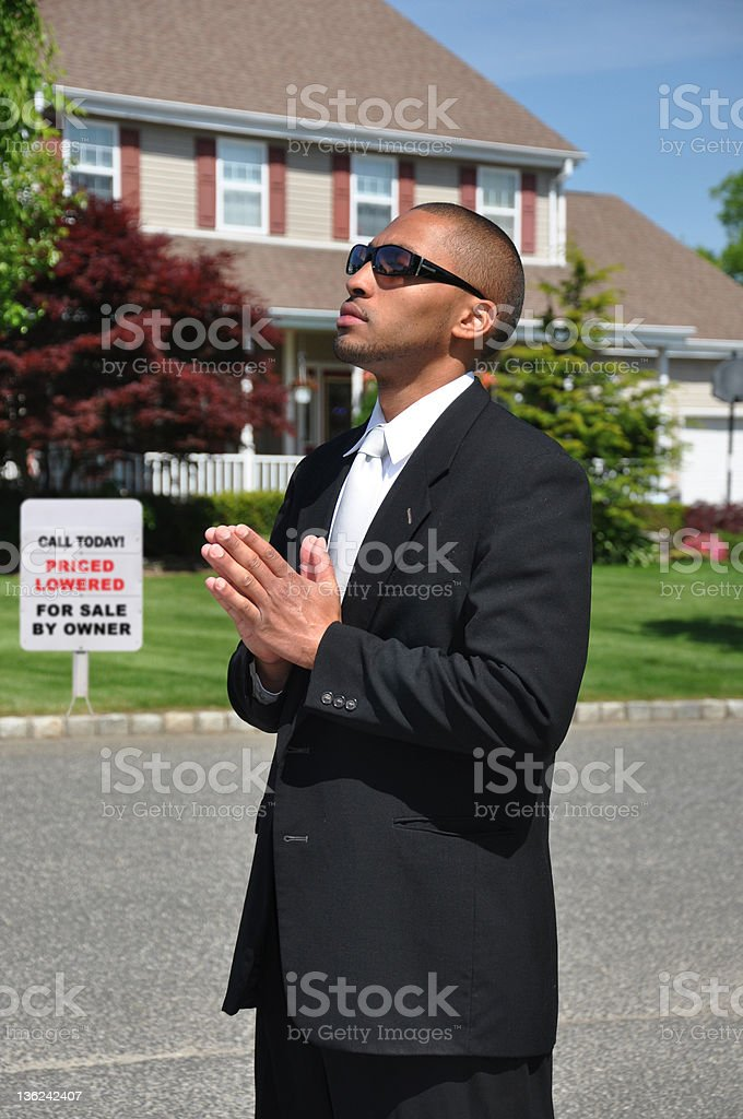 Young Man Praying Hands in Suburban Neighborhood stock photo