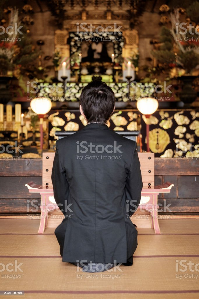 Young Man Praying in Buddhist Temple stock photo