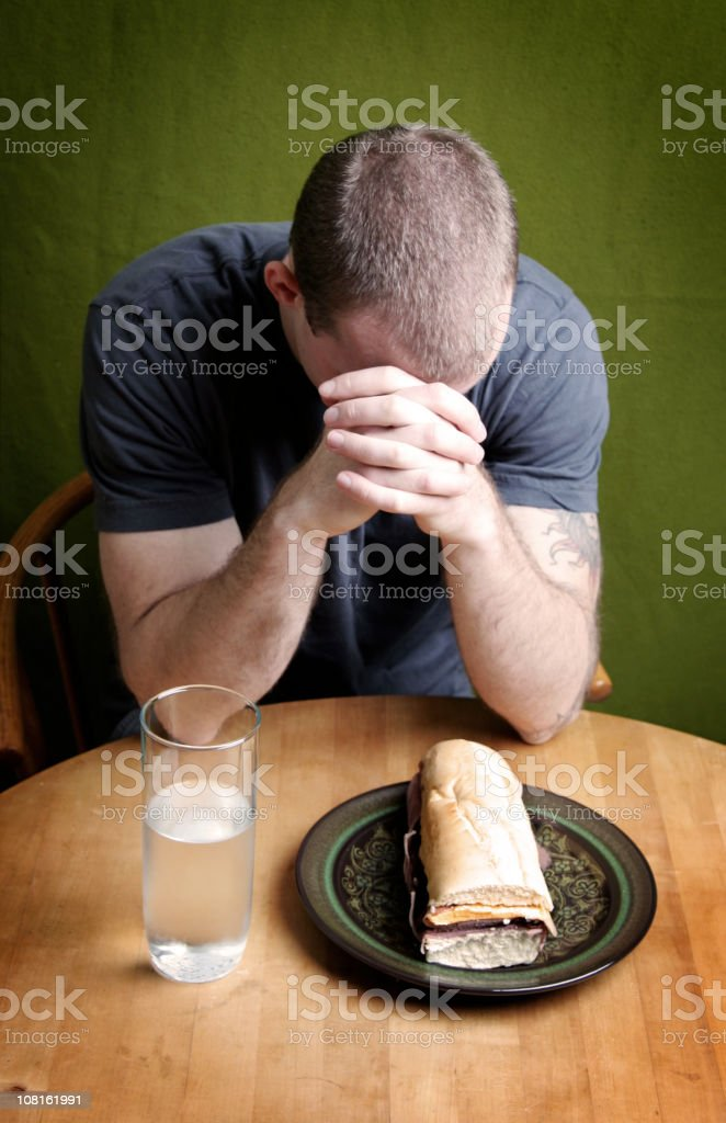 Young Man Prays Thanks For His Meal royalty-free stock photo