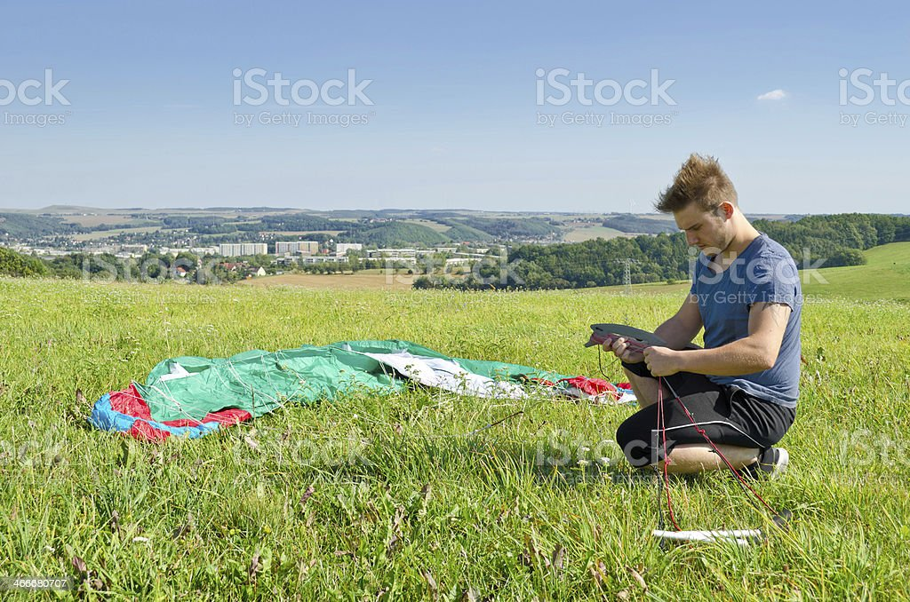 Young man prepairing a kite for kiting stock photo
