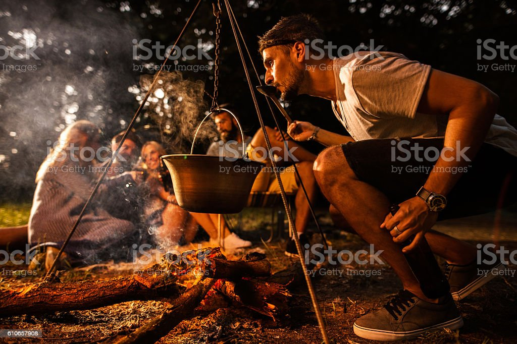Young man preparing food while camping with his friends. stock photo