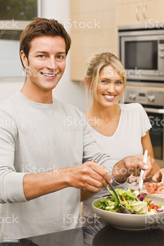 Young man preparing salad and woman standing beside stock photo