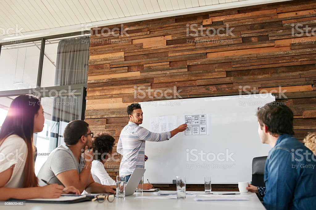 Young man presenting new app design to colleagues stock photo