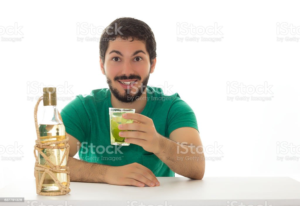 Young man presents a glass with lemon-based cocktail and cachaca stock photo