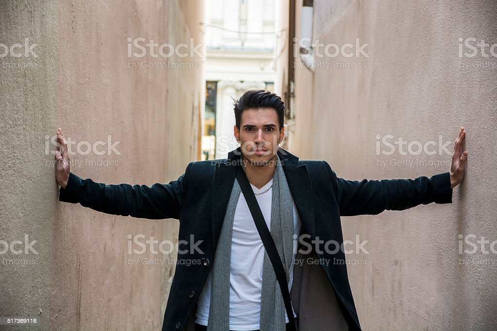 Young man pressed between two walls. Oppression, anxiety stock photo