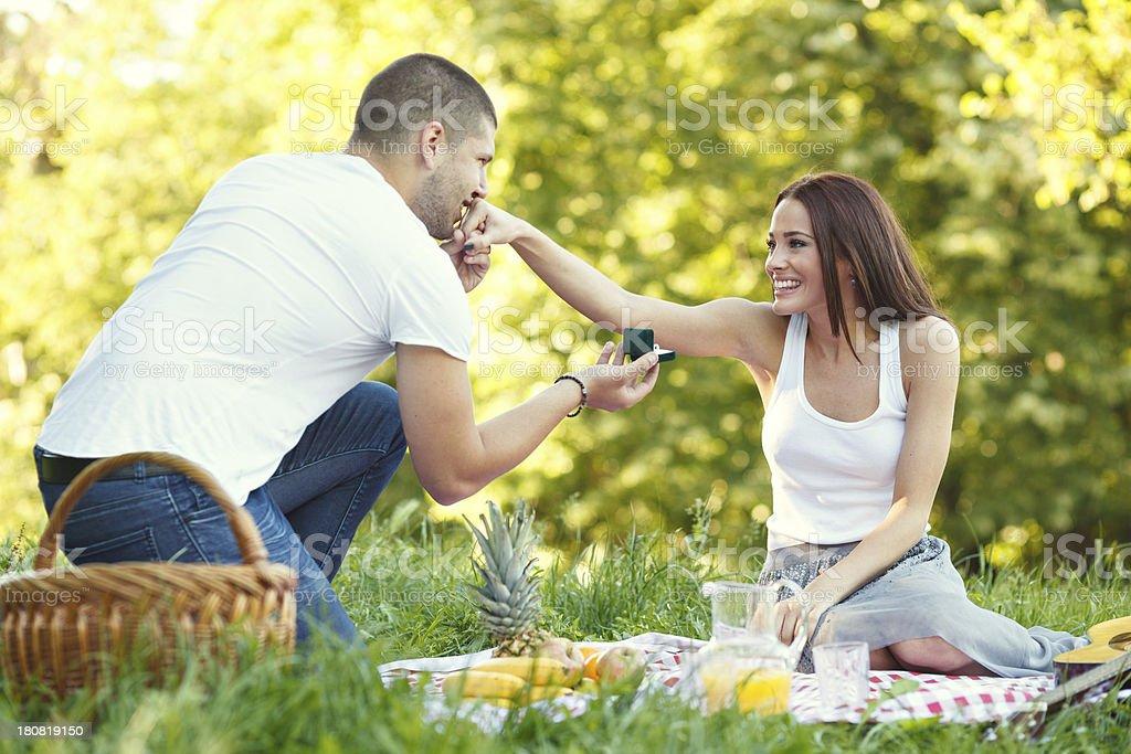 Young man proposing his beautiful girlfriend royalty-free stock photo