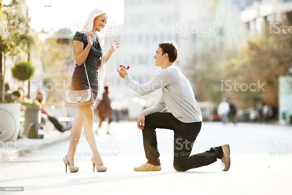 Young man proposing to a woman. stock photo